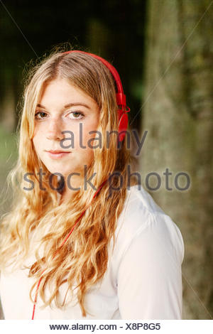 Portrait of young woman wearing headphones at park - Stock Photo