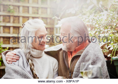 Senior couple wrapped in blanket in garden - Stock Photo