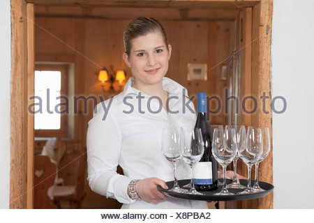 waitress with bottle of wine and glasses - Stock Photo