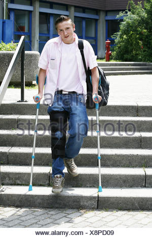 Stairs, young person, feet, knees, injury, crutches, rail, knee injury, trousers, jeans, bandage, knee prop, bone prop, black, accident, impediment, unwieldy, danger, insurance, encroachment, walking impediment, healing, accessory, person, schoolboy, whole body, - Stock Photo