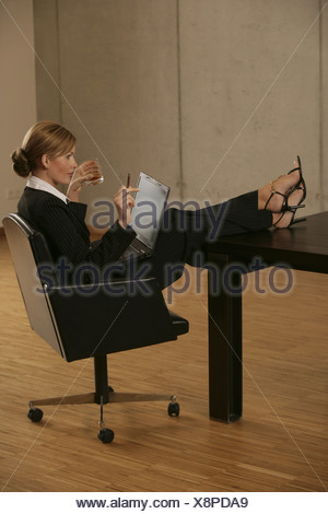 A blonde businesswoman smoking and drinking with a laptop on her lap - Stock Photo