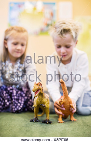 Children playing with toy dinosaurs in kindergarten - Stock Photo