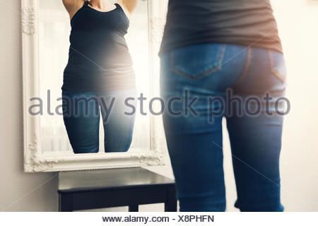 anorexia concept - woman looks at her fat reflection in mirror - Stock Photo