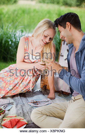 Young couple picnicking and toasting wine glasses in park - Stock Photo