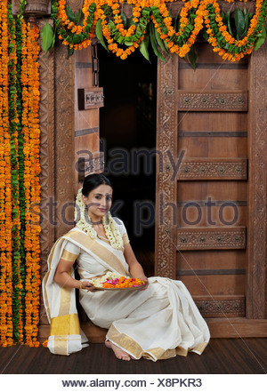 South Indian woman holding a tray - Stock Photo