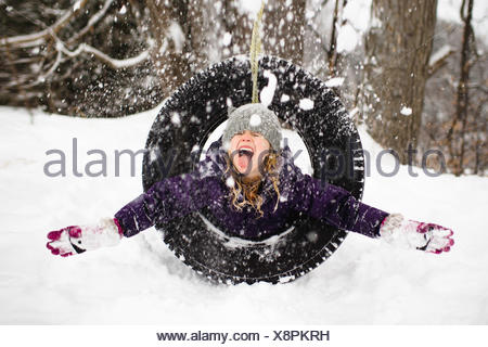 Girl playing in snow on tire swing - Stock Photo