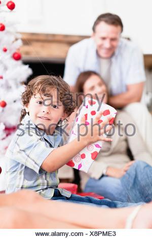 Boy shaking wrapped Christmas gift - Stock Photo