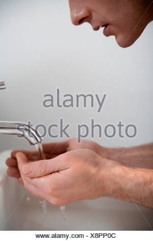 Man cupping hands under faucet - Stock Photo