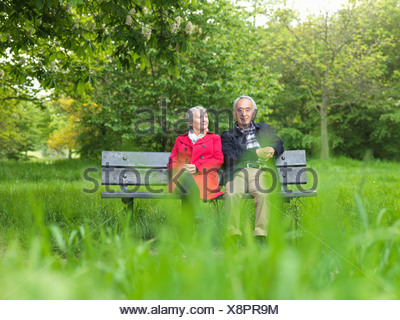 Older couple sitting on park bench - Stock Photo