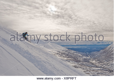 A woman backcountry skier enjoys some powdery turns in Hatcher Pass, Alaska - Stock Photo