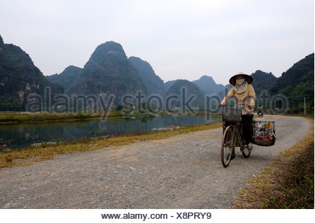 Vietnamese woman on bicycle collecting trash in front of karst mountains, National Park TamCoc, Ninh Binh, North Vietnam, South - Stock Photo