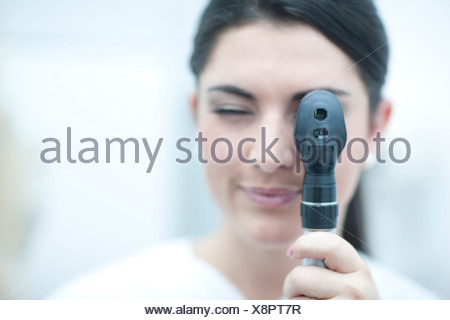 Portrait of optician looking through ophthalmoscope - Stock Photo