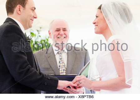 Bride putting ring on grooms finger - Stock Photo