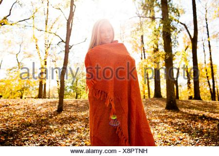 Portrait of young woman wrapped in blanket in autumn forest - Stock Photo