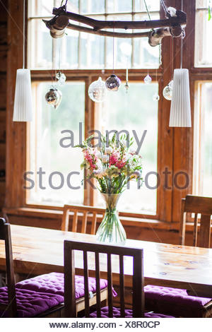 Vase with flowers on dining table - Stock Photo
