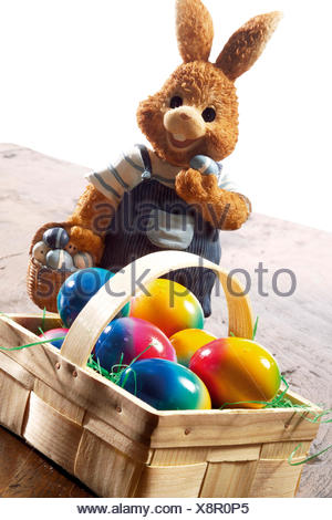 Easter bunny with basket filled with coloured eggs - Stock Photo