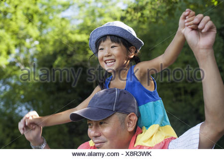 Father carrying his daughter on his shoulders. - Stock Photo