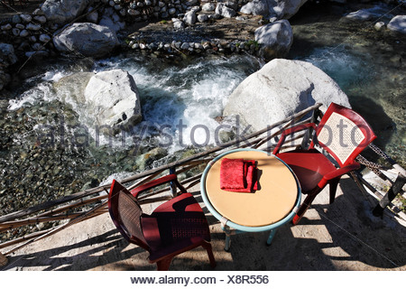 Two red chairs and a table at a restaurant patio overlooking mountain rapids, Ourika Valley, High Atlas Range, Morocco, North A - Stock Photo