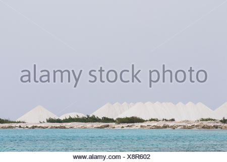 Mountains of salt collected in salt pans by the Cargill Salt Works on the southwest of Bonaire Island. - Stock Photo