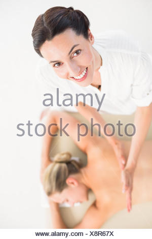 Peaceful blonde getting facial massage from beauty therapist - Stock Photo