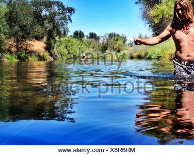 Young Man Walking On Lake Against Sky - Stock Photo