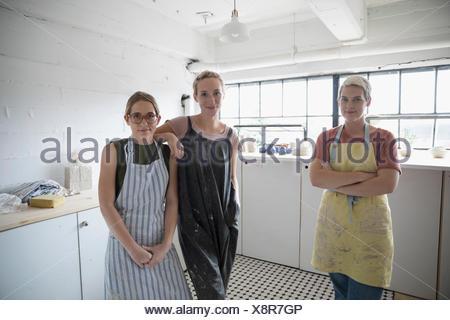 Portrait confident female potters in aprons in art studio - Stock Photo
