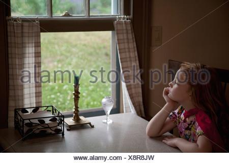 Thoughtful girl looking through open window - Stock Photo