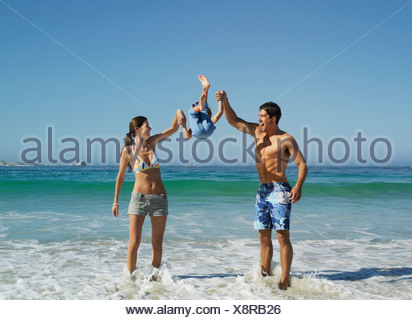 Parents swinging son 5 7 up into air standing in surf on beach smiling front view - Stock Photo