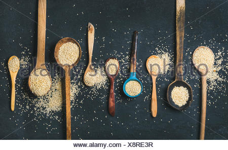 Quinoa seeds in different spoons over black stone background, top view. Superfood, healthy eating, dieting, clean eating, detox or vegetarian food con - Stock Photo