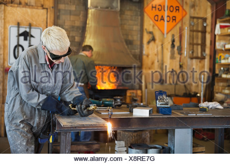 Female welder cutting metal with torch - Stock Photo