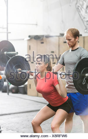 Man assisting woman in lifting barbell in crossfit gym - Stock Photo