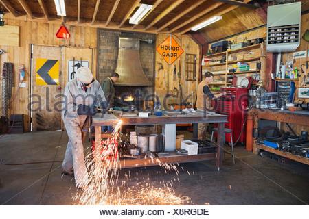 Female welder using welding torch in workshop - Stock Photo