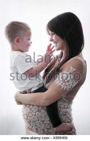 A pregnant woman holding her young son in her arms. - Stock Photo