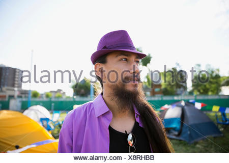 Young man with long hair and beard wearing purple hat looking away at summer music festival campsite - Stock Photo