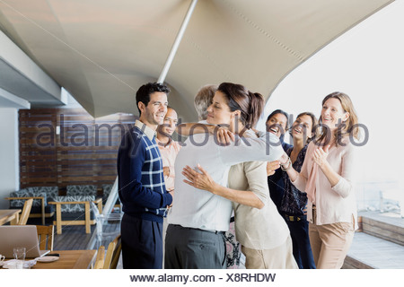 Business people hugging in office - Stock Photo