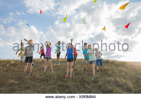 Schoolchildren throwing paper airplanes on hillside - Stock Photo