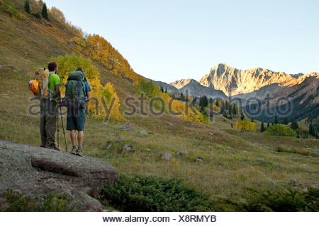 Two young men hiking look out at beautiful mountains and the fall colors. - Stock Photo