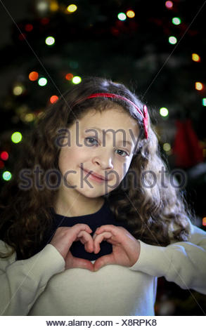 Girl making heart shape with hands in front of Christmas tree - Stock Photo