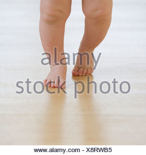 Close up of baby's feet walking - Stock Photo