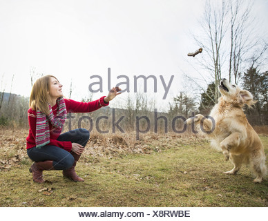 A young woman outdoors in the winter on a walk with a golden retriever dog - Stock Photo