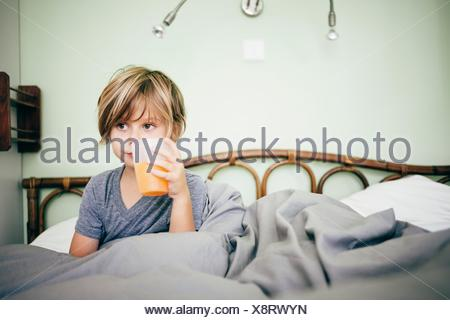Boy sitting in bed drinking beaker of orange juice, looking away, Bludenz, Vorarlberg, Austria - Stock Photo