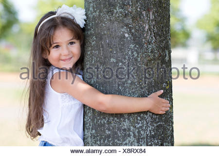Portrait of smiling little girl hugging a tree - Stock Photo