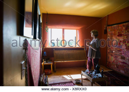 Pensive woman drinking coffee looking out window - Stock Photo
