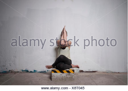 Mid adult woman practicing cow face pose in yoga studio, Munich, Bavaria, Germany - Stock Photo