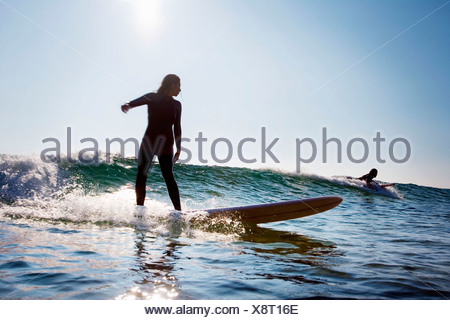 Man and woman surfing. - Stock Photo