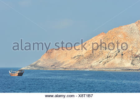 A fishing boat close to Al Qibliyah island, one of the Hallaniyat islands, coast of Dhofar, Oman, Arabian Sea - Stock Photo