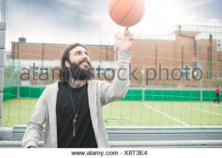 Mid adult man spinning basketball on finger - Stock Photo