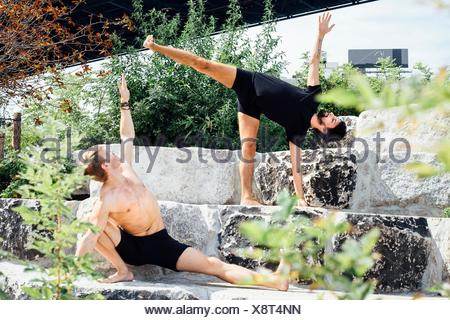 Two men practicing yoga positions together on park step - Stock Photo