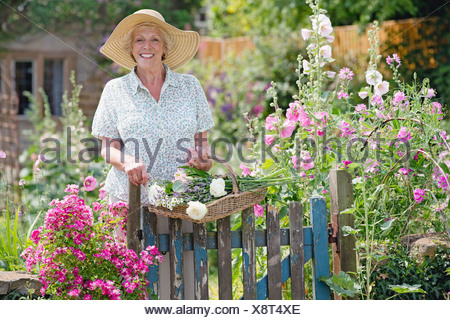 Senior Woman In Garden Of Beautiful Cottage - Stock Photo