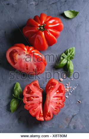 Whole and sliced organic tomatoes Coeur De Boeuf. Beefsteak tomato with pink salt and basil on blue gray metal texture background. Top view with space - Stock Photo